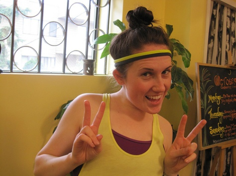 Picture of a young woman in athletic clothes wearing a headband with her hair in a bun.