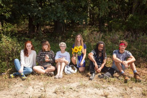 Six students sit underneath some trees near a sunflower patch